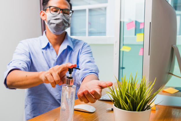 how to design the workplace for social distancing - business man working from home office he quarantines disease coronavirus wearing protective mask cleaning hands with sanitizer gel 143683 3191 - How to Design the Workplace for Social Distancing
